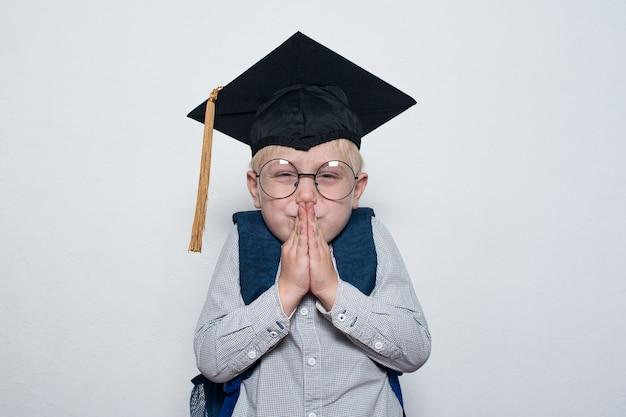 Kleine jongen die een studentenhoed draagt. wit. sluwe schooljongen beraamde een grap. portret op halve lengte.