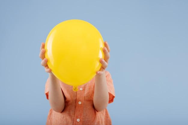 Kleine jongen die gezicht bedekt met gele ballon, geïsoleerd op blauwe achtergrond, kopieer ruimte