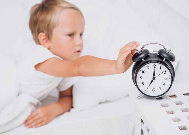 Kleine jongen die het alarm stopt