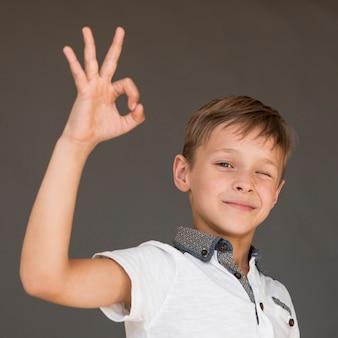 Kleine jongen die het ok teken geeft