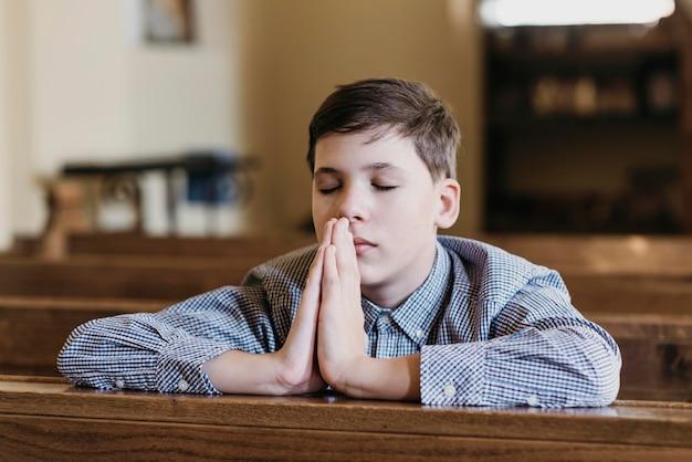 Kleine jongen die in de kerk bidt