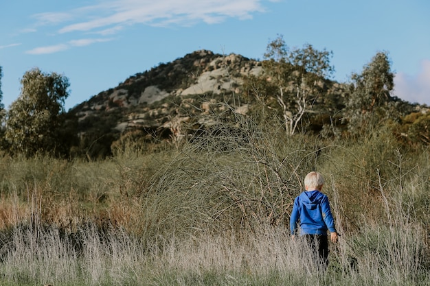Kleine jongen die in het veld loopt met een bergachtig landschap erachter