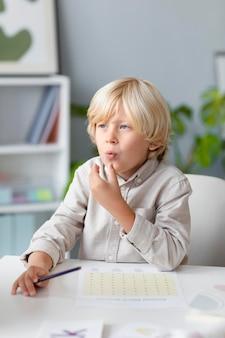 Kleine jongen die logopedie beoefent