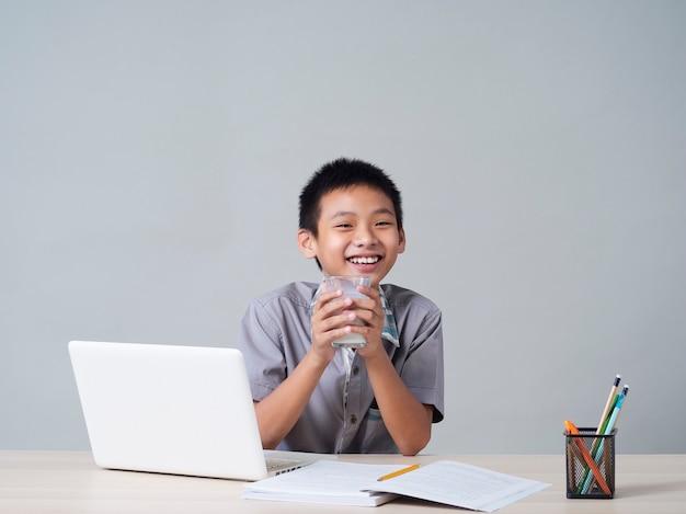 Kleine jongen die melk drinkt terwijl hij thuis online studeert