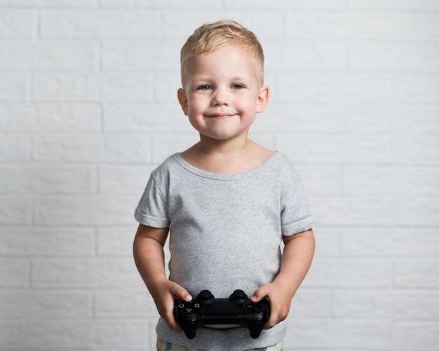 Kleine jongen die met bedieningshendel camera bekijkt