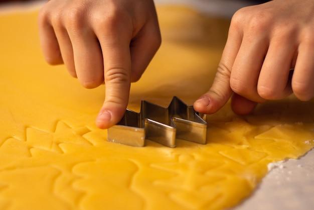Kleine jongen die metalen vorm gebruikt om deeg te snijden en kerstkoekjes te maken