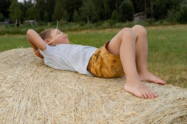 Kleine jongen die op hooizak ligt met een rietje in zijn mond karelia regio rusland
