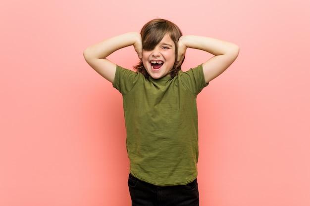 Kleine jongen die oren bedekt met handen die niet te hard geluid proberen te horen.