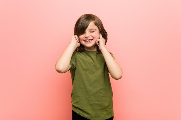 Kleine jongen die oren bedekt met handen.