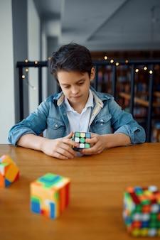 Kleine jongen die puzzelkubussen probeert op te lossen. speelgoed voor training van hersenen en logische geest, creatief spel, oplossen van complexe problemen