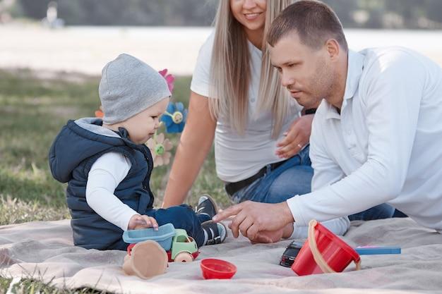 Kleine jongen die speelgoedauto's speelt en plezier heeft met zijn vader en moeder buitenshuis