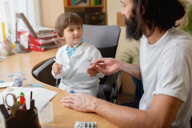 Kleine jongen die speelt doet alsof hij een dokter is die een man in een comfortabel medisch kantoor onderzoekt. gezondheidszorg, jeugd, geneeskunde, bescherming en geluk concept. plezier maken, lachen terwijl je pillen geeft recept
