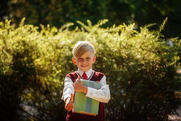 Kleine jongen die terug naar school gaat. kind met rugzak en boeken op de eerste schooldag