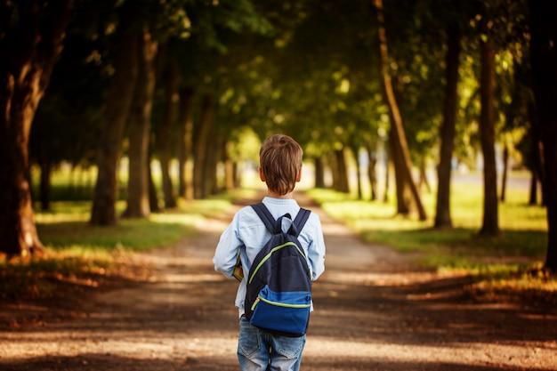 Kleine jongen die terug naar school gaat. kind met rugzak en boeken.