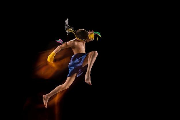 Kleine jongen die thai boksen op zwarte muur uitoefent. gemengd licht. vechter oefenen in vechtsporten in actie, beweging. evolutie van beweging, vangmoment. jeugd, sport, aziatisch cultuurconcept.