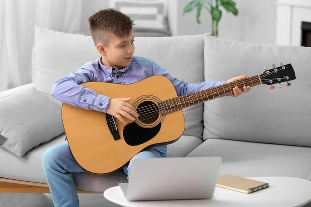 Kleine jongen die thuis muzieklessen neemt