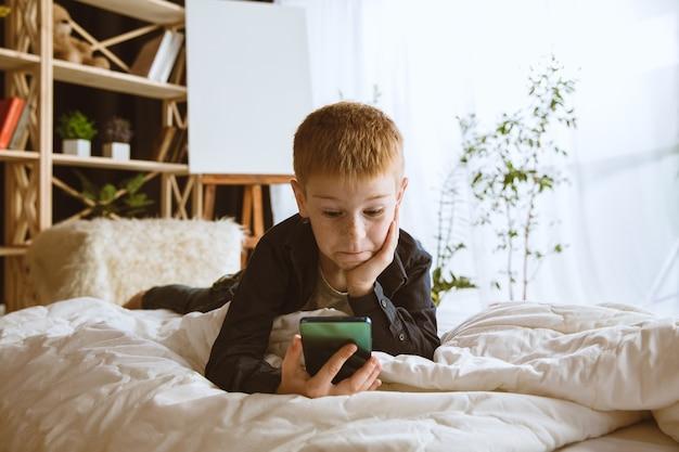 Kleine jongen die thuis verschillende gadgets gebruikt
