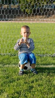 Kleine jongen die verfrissend vruchtensap drinkt terwijl hij een pauze neemt, zittend op de bal in de doelen tijdens het voetballen