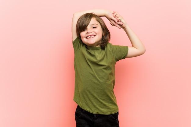 Kleine jongen die zich uitstrekt armen, ontspannen positie.