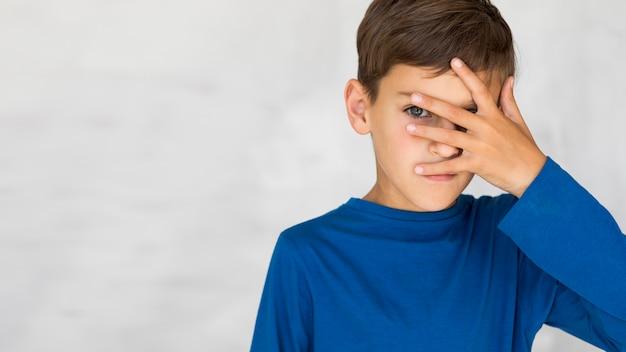 Kleine jongen die zijn gezicht bedekt met de hand