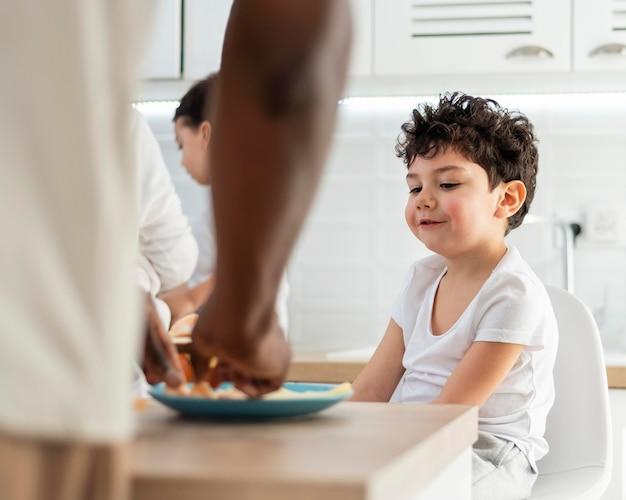 Kleine jongen die zijn ontbijt heeft, bereid door zijn vader