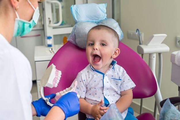Kleine jongen die zijn tanden toont aan een arts