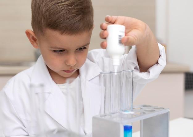 Kleine jongen doet een wetenschappelijk experiment op school