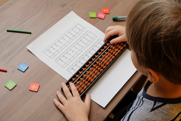 Kleine jongen doet eenvoudige wiskundeoefeningen met telraamscores. hoofdrekenen. uitzicht vanaf de schouder