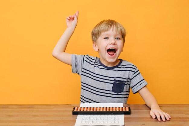 Kleine jongen doet eenvoudige wiskundeoefeningen met telraamscores. hoofdrekenen.