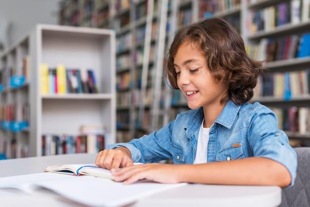 Kleine jongen doet zijn huiswerk in de bibliotheek