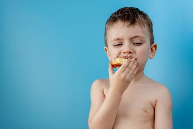 Kleine jongen donut chocolade eten. leuke gelukkige jongen besmeurd met chocolade rond zijn mond. kind concept, lekker eten voor kinderen