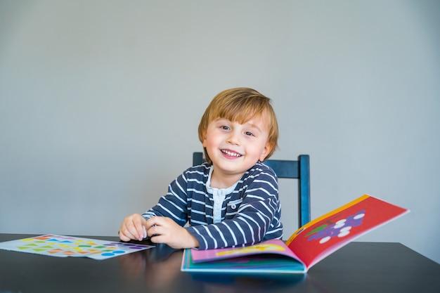 Kleine jongen draagt een gestreept t-shirt aan de tafel, leert thuis tijdens de coronavirus-quarantaine. peuter spelen met gevormde stickers.