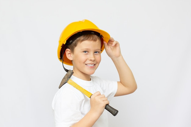 Kleine jongen draagt een helm en houdt een hummeer op de witte achtergrond. bouw, reparatie, interieur.