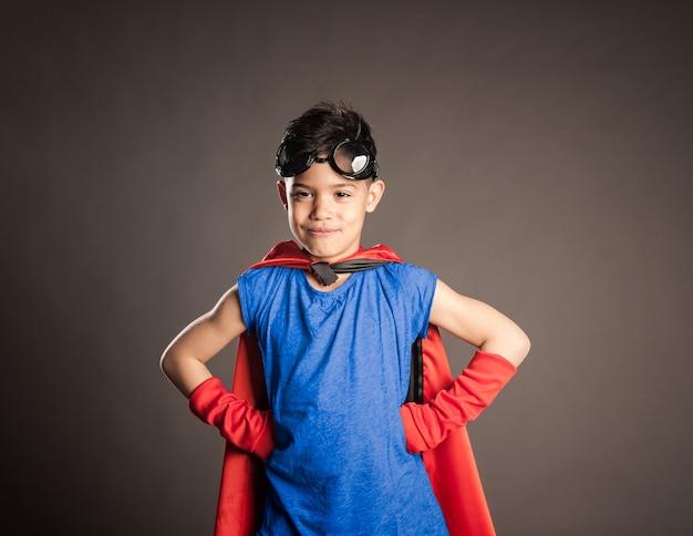 Kleine jongen draagt een superheld kostuum op grijs
