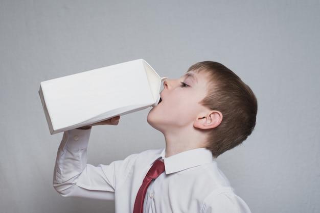 Kleine jongen drinkt uit een groot wit pakket. wit overhemd en rode stropdas