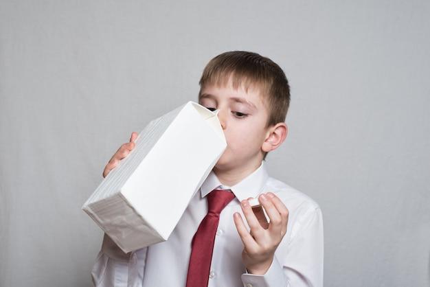 Kleine jongen drinkt uit een grote witte verpakking. wit overhemd en rode stropdas.
