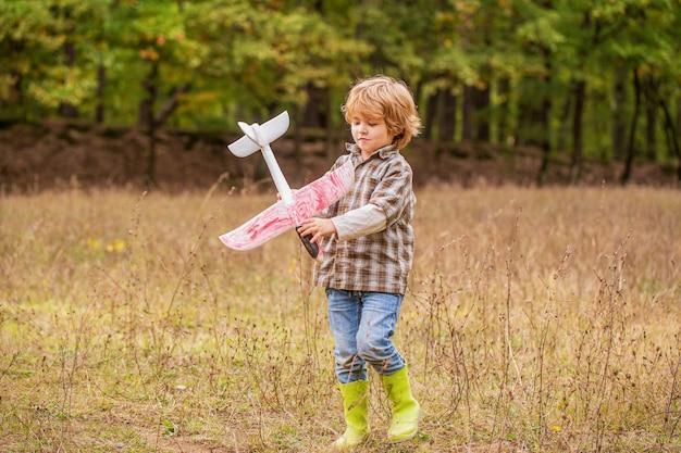 Kleine jongen droomt ervan piloot te worden. kind spelen met speelgoed vliegtuig. gelukkig kind spelen. gelukkig kind buiten spelen. het gelukkige vliegtuig van het jongensspel.