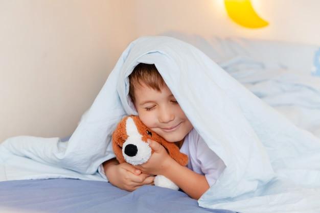 Kleine jongen droomt van huisdier, liggend op zijn bed en speelgoedhond knuffelen
