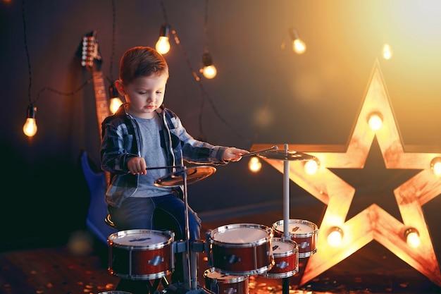 Kleine jongen drummen op het podium