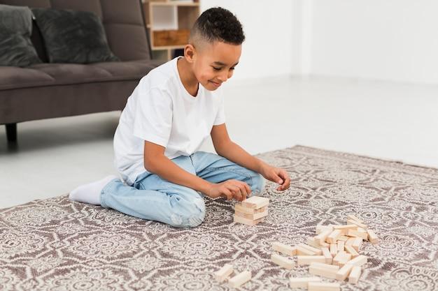 Kleine jongen een houten toren spel spelen