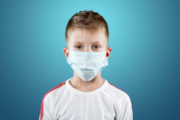 Kleine jongen, een kind in een medisch masker op een blauw
