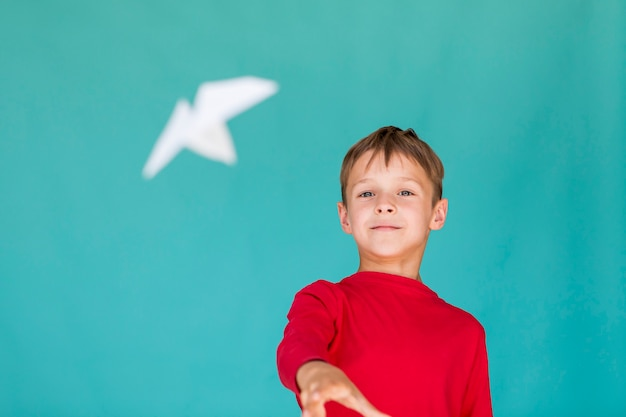 Kleine jongen een papieren vliegtuigje gooien