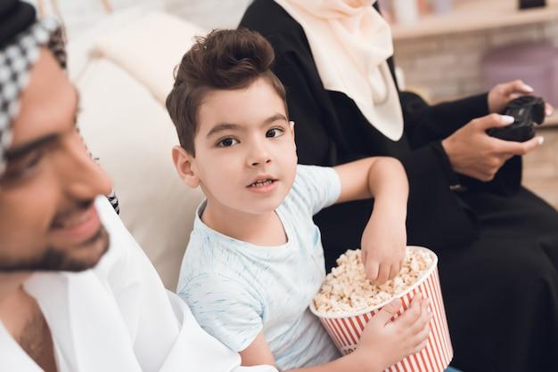 Kleine jongen eet popcorn terwijl zijn familie een gameconsole speelt