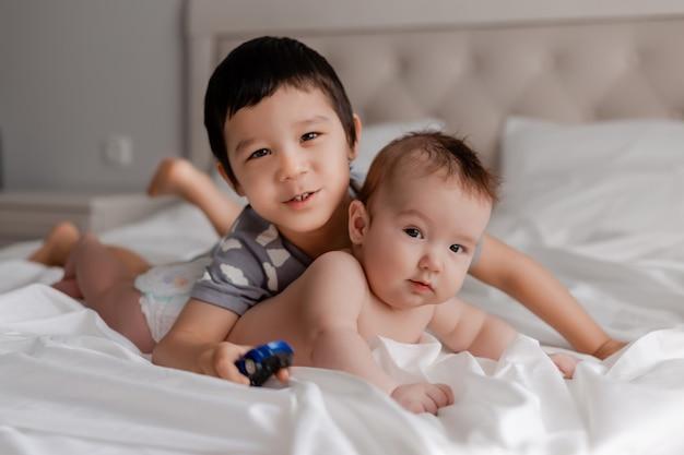 Kleine jongen en een baby twee broers liggen op wit beddengoed in bed en knuffelen