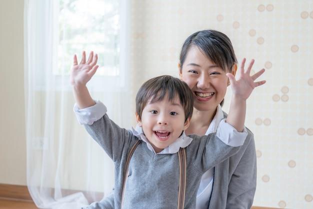Kleine jongen en jonge moeder lacht en speelt samen