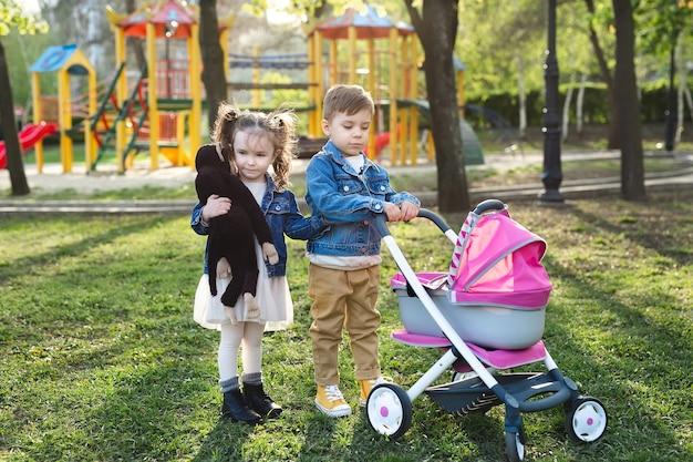Kleine jongen en kleine meisjesbaby lopen met een wandelwagen voor poppen