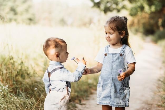 Kleine jongen en meisje, broer en zus spelen samen in de natuur in de zomer