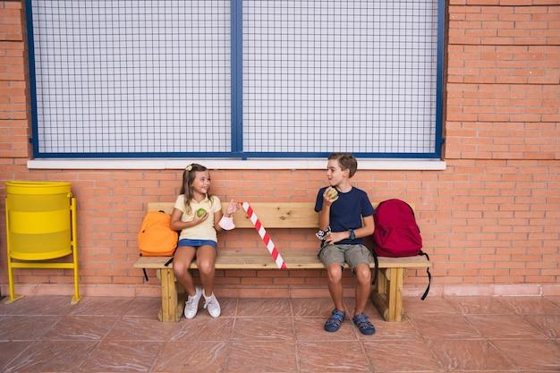 Kleine jongen en meisje die een appel eten tijdens de pauze zittend op een bankje sociale afstand houden. terug naar school tijdens covid pandemic.