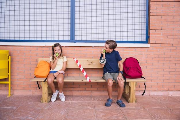 Kleine jongen en meisje die een appel eten tijdens de pauze zittend op een bankje sociale afstand houden.