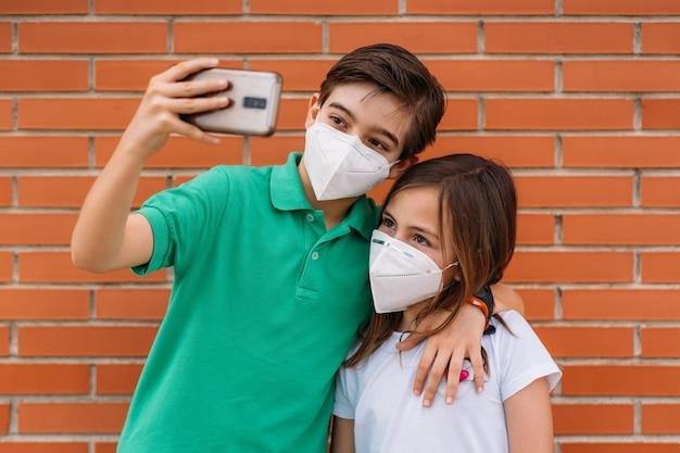 Kleine jongen en meisje dragen maskers en nemen een selfie